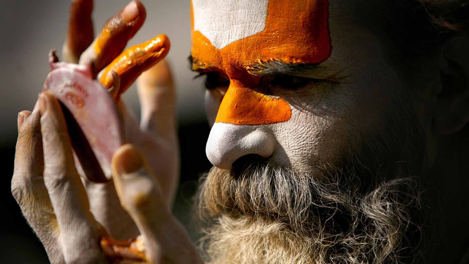 A sadhu (holy man) smearing colourful powder on forehead on the Pashupatinath temple premises, Kathmandu on Thursday. Photo: NAVESH CHITRAKAR